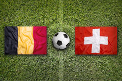 Belgium vs. Switzerland flags on soccer field Royalty Free Stock Photos