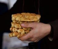 Belgium waffle, belgium food, typical belgium sweet, fragment photo, man holding belgium waffle in his hand with blurry dark backg Royalty Free Stock Photo