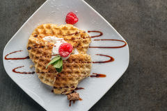 Belgium waffle topped with chocolate topping, whipped cream and fresh raspberries on top on white plate, product photography Royalty Free Stock Photo