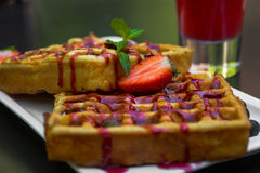 Belgium waffle topped with syrup and freshly chopped strawberrie Stock Images