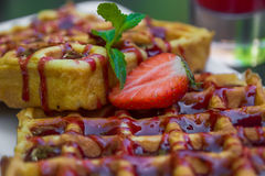 Belgium waffle topped with syrup and freshly chopped strawberrie Royalty Free Stock Photos