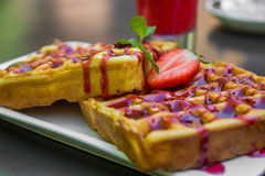 Belgium waffle topped with syrup and freshly chopped strawberrie Royalty Free Stock Images