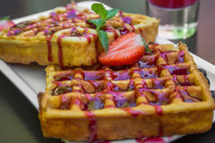 Belgium waffle topped with syrup and freshly chopped strawberrie Stock Image