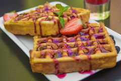 Belgium waffle topped with syrup and freshly chopped strawberrie Stock Photo