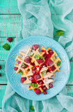 Belgium waffles with raspberries and syrup. On a plate royalty free stock image