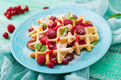 Belgium waffles with raspberries and syrup Stock Images