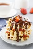 Belgium waffles with strawberries, banana and flowing chocolate stock photos