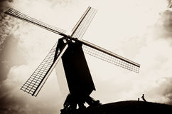 Belgium windmill. A silhouette of two kids playing next to a hilltop Windmill on a cloudy day.This is one of a series of windmills next to each other in Brugge Stock Photography
