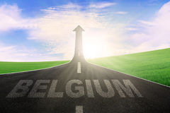 Belgium word on road with arrow upward. Empty road with word of Belgium and arrow upward at the end of a road Royalty Free Stock Photos