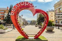 Belgorod, Rússia Ambiente da cidade Banco do amor na forma de um coração com potenciômetros de flor Imagem de Stock
