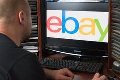 Belgorod, Rusia - 11 de diciembre de 2017: El hombre es Ebay Un hombre blanco que se sienta en el ordenador En el monitor antes e foto de archivo