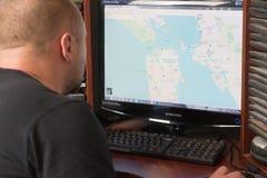 Belgorod, Rusia - 11 de diciembre de 2017: El hombre utiliza Google Maps Un hombre blanco que se sienta en el ordenador En el mon imagen de archivo