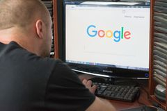 Belgorod, Russia - December 11, 2017: Man uses Google search. A white man sitting at the computer. On the monitor before his eyes royalty free stock image
