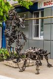 Street metal sculpture of a robot with machine gun and robot dog made of old cars parts and details, auto-waste. Stock Image