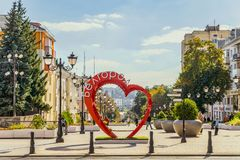 Pedestrian street in the old residential center of the city. Bench of love in the shape of a heart with flower pots. Stock Image