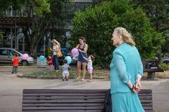 BELGRAD, SERBIEN - 2. AUGUST 2015: Alte Frau, welche die jüngeren Frauen sich kümmern um den Kindern spielen mit Ballonen im Voro Stockfotografie