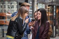 BELGRAD, SERBIEN - 25. MAI 2017: Jungen und Mädchen der jungen Leute, Mann und Frau, die zusammen einen Smartphone und ein Lächel Stockfotografie