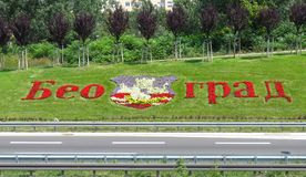 Belgrade made of flowers. Belgrade name and coat of arms made of flowers in grass by the highway and Genex tower,the gate of the city royalty free stock photography