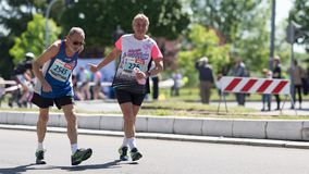 Elderly man and woman running marathon, encouraging each other stock images