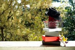 Shopping basket with red purse and small black female hat with v royalty free stock photo