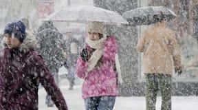 One teenage girl walking under umbrella in heavy snowfall stock image