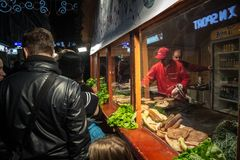 Crowd packing in front of a Rostilj stand with beef pattys pljeskavica, meat fingers cevapi and sausages ready. stock images