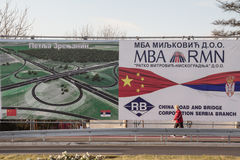 BELGRADE, SERBIA - DECEMBER 25, 2014: Woman passing by a billboard promoting Chinese investments in Serbia near the newly opened P royalty free stock photos