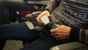 BELGRADE, SERBIA - FEBRUARY 2014: View of a man fastening his seat belt. Safe travel is of great importance while traveling in air. Plane stock video footage
