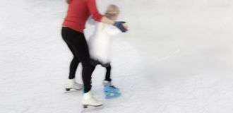 Teaching new skill ice skating to a chilld Royalty Free Stock Photography