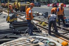 Worker work on road repair. BELGRADE, SERBIA - JULY 29, 2017: Worker work on road repair and installation tram line. Cutting tram rails Royalty Free Stock Image