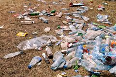 Plastic pet bottles left on grass after an party, event. Used empty bottles thrown away on the ground after an open air party. Stock Images