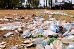 Plastic pet bottles left on grass after an party, event. Used empty bottles thrown away on the ground after an open air party. stock photography