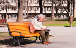 Nice weather. BELGRADE, SERBIA - MARCH 12 Pensioner sitting on a park bench and reading newspapers while waiting for the beginning of spring on March 12, 2013 in Stock Image
