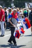 Man selling Serbian flags during sunny summer day stock photography