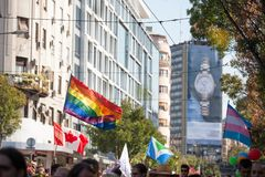 Crowd raising and holding rainbow gay flags and canadian flag, during the Belgrade Gay Pride. royalty free stock photos