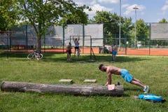 BELGRADE SERBIEN - JUNI 04, 2017: Praktiserande utomhus- genomkörare för unga män på den Ada Ciganlija ön, i Belgrade Arkivbilder
