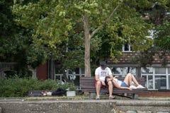 BELGRADO, SÉRVIA - 2 DE AGOSTO DE 2015: Amantes que descansam em um banco, um sono desabrigado no fundo, distrito de Zemun, Belgr Imagem de Stock Royalty Free