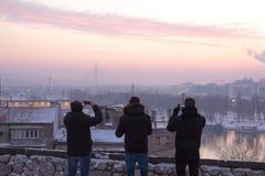 BELGRADO, SÉRVIA - 1º DE JANEIRO DE 2015: três homens novos que tomam imagens do panorama de Belgrado no crepúsculo da fortaleza  Imagem de Stock Royalty Free