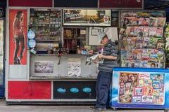 BELGRADO, SERBIA - 2 AGOSTO 2015: Uomo anziano che legge un giornale ad un chiosco Trafika di estate nella capitale della Serbia  fotografia stock