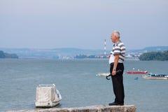 BELGRADO, SERBIA - 2 DE AGOSTO DE 2015: Viejo hombre observando el centro de Belgrado y el Danubio del suburbio de Zemun en un dí Foto de archivo libre de regalías
