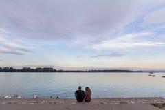 BELGRADO, SERBIA - 2 DE OCTUBRE DE 2016: Amantes que miran junto el río Danubio en caída en el banco del distrito de Zemun Foto de archivo