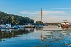 Belgrado, Serbia - 20 giugno 2018: Vista laterale del ponte del Ada con la riflessione sopra il porticciolo di Belgrado sul fiume immagine stock