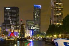 Belichtete alte Kräne und moderne Bürogebäude nachts im historischen Hafen von Rotterdam Stockbilder