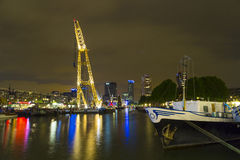 Belichtete alte Kräne und moderne Bürogebäude nachts im historischen Hafen von Rotterdam Lizenzfreies Stockfoto