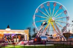 Belichtete Anziehungskraft Ferris Wheel On Summer Evening in der Stadt-Unterhaltung Stockfotografie