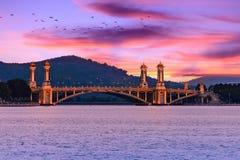 Belichtete Brücke über dem Fluss, Dämmerung, Ansicht über Putra See glättend lizenzfreie stockfotos