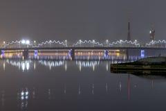 Belichtete Eisenbahnbrücke Rigas über Fluss Daugava nachts, Lettland lizenzfreie stockfotografie