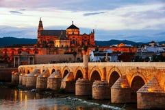 Belichtete römische Brücke und La Mezquita bei Sonnenuntergang in Cordoba, Spanien stockbild