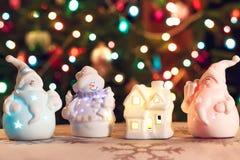 Belichtete Schneemann- und Jack Frost-(Santa Claus) Puppen vor Christbaumkerzen, unscharfer Hintergrund Lizenzfreie Stockfotos