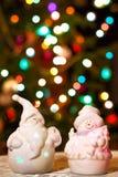 Belichtete Schneemann- und Jack Frost-(Santa Claus) Puppen vor Christbaumkerzen, unscharfer Hintergrund Lizenzfreie Stockbilder